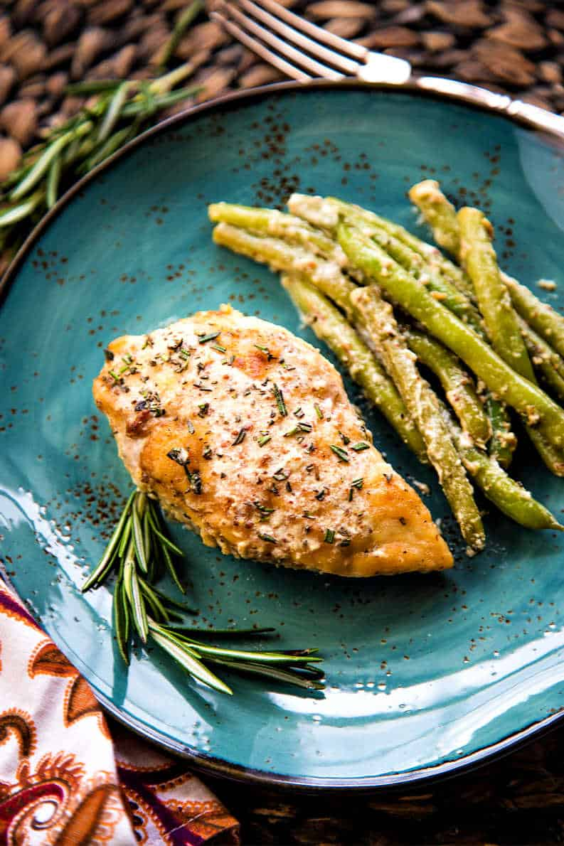 rosemary dijon chicken with whole green beans on a blue plate