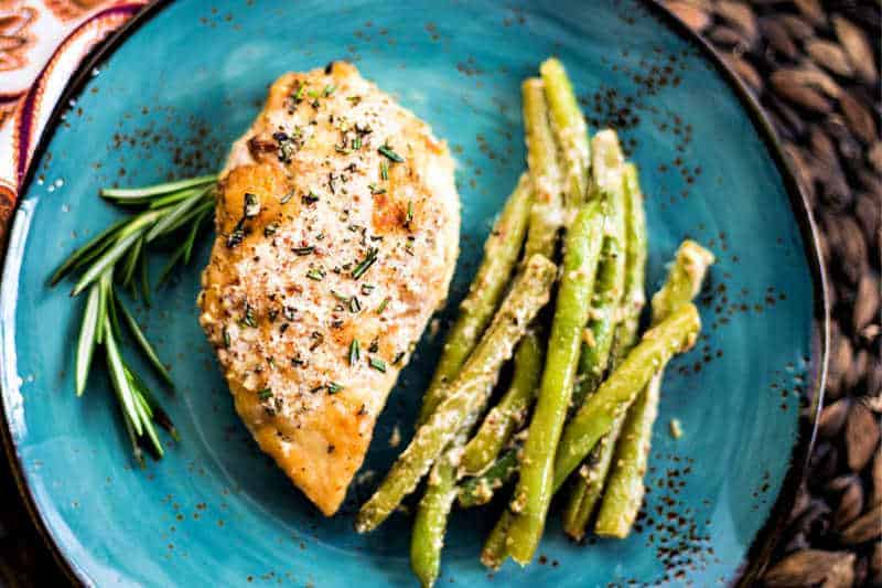 a blue plate with chicken and green beans garnished with a sprig of rosemary