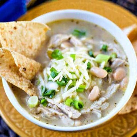 A bowl of food on a plate, with white chicken chili