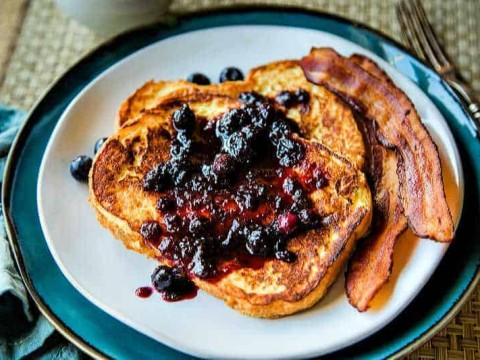 two slices of french toast on a white plate with bacon and berry preserves