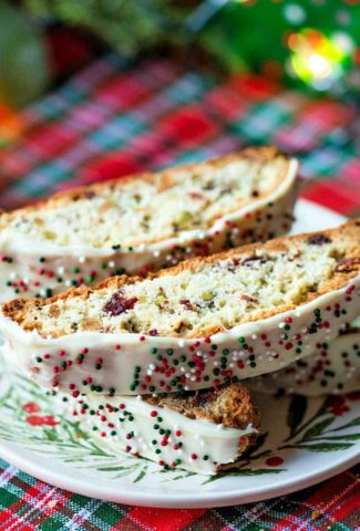 pieces of cranberry pistachio biscotti on a Christmas plate setting on a red and green plaid table cloth