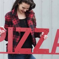 woman holding a red pizza sign