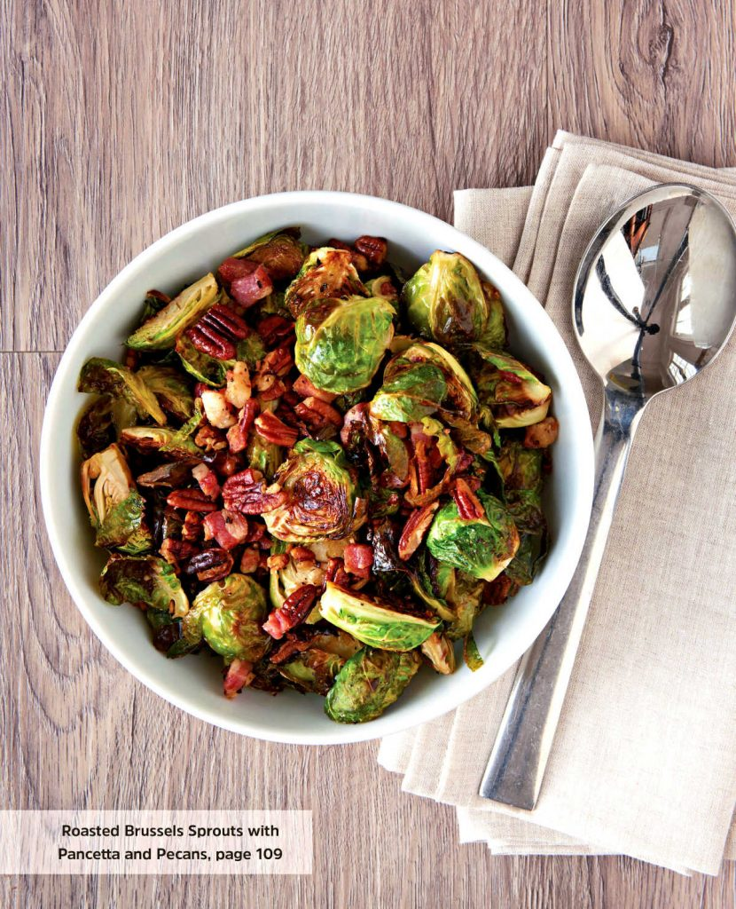 A bowl of Brussels sprouts wth pancetta and pecans on a wooden background with a serving spoon