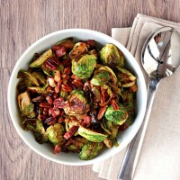 Roasted Brussels Sprouts with Pancetta and Pecans in a white bowl with a silver serving spoon