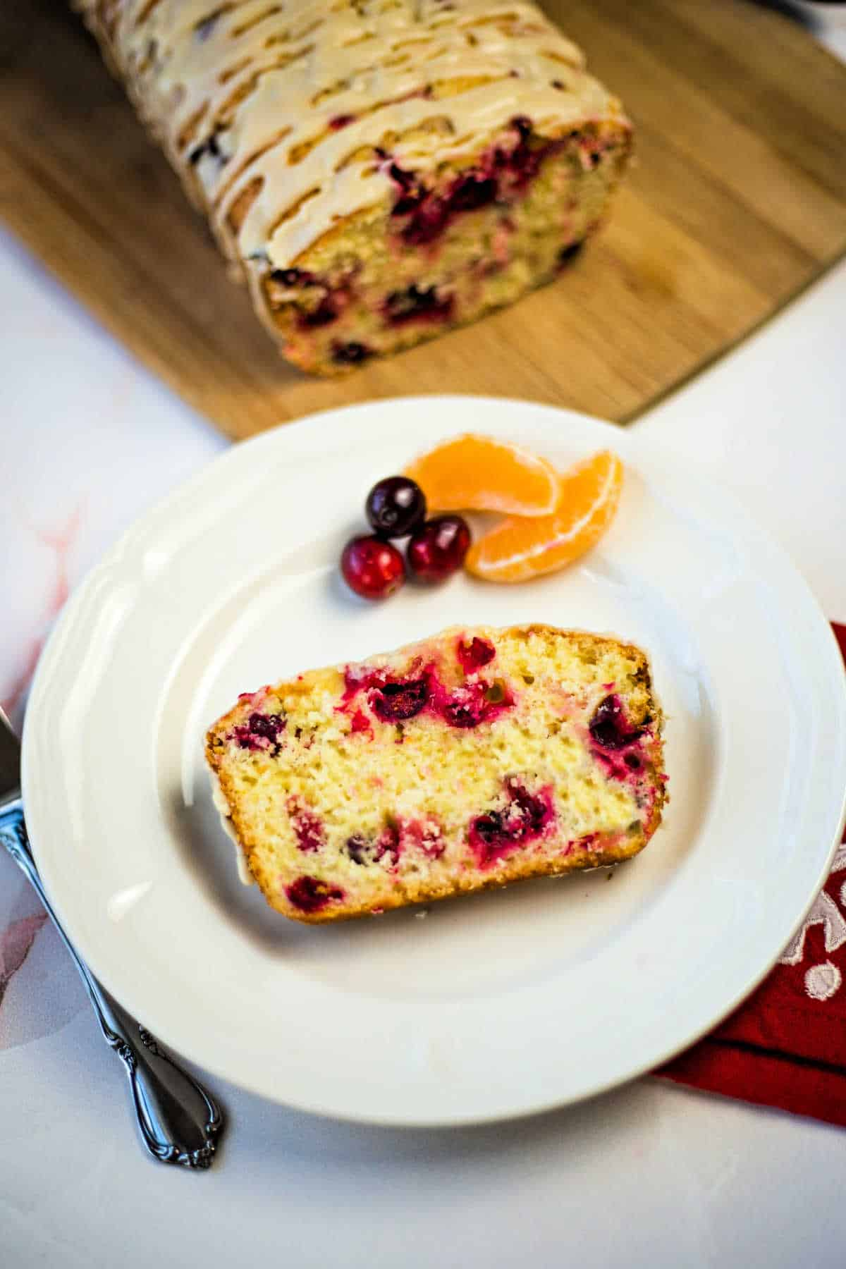a slice of cranberry orange bread on a white plate with orange segments and cranberries