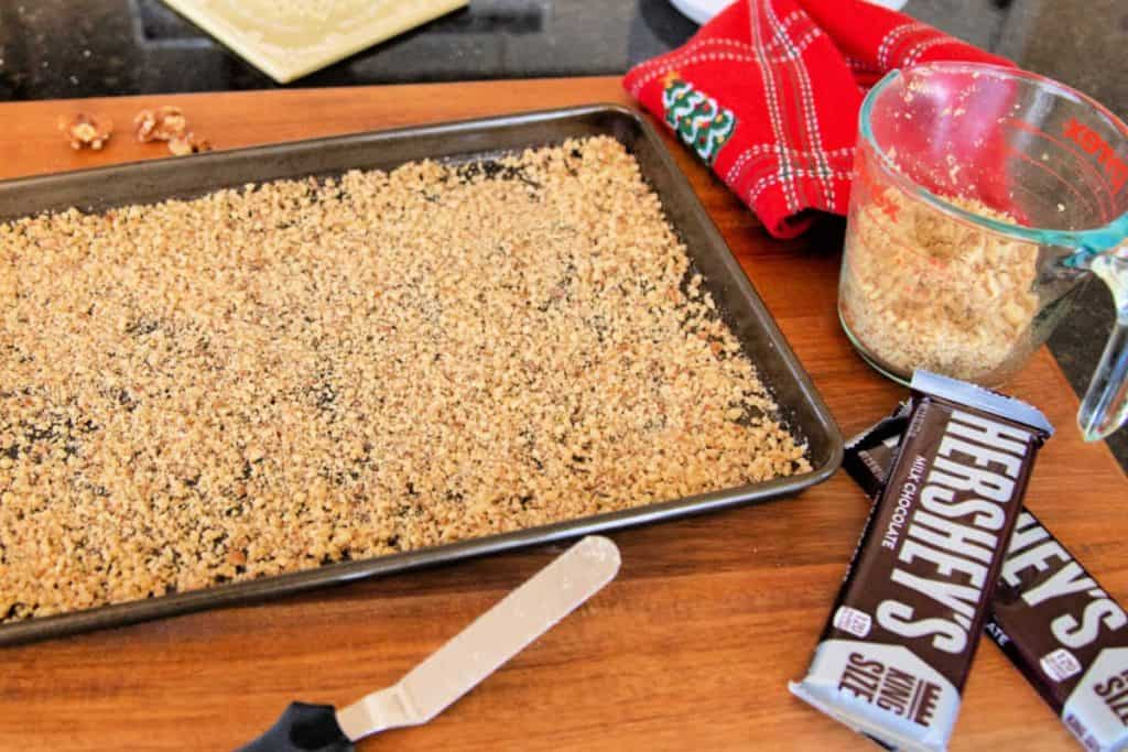 baking sheet with a layer of chopped walnuts, 2 Hershey chocolate bars, and an off set spatula on a counter