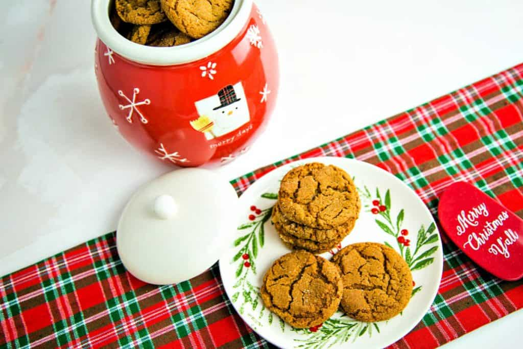 a snowman cookie jar with a plate of ginger cookies on a red and green plaid table runner