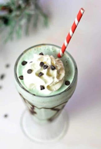 top down view of mint chocolate chip milkshake in a soda glass with a red striped straw