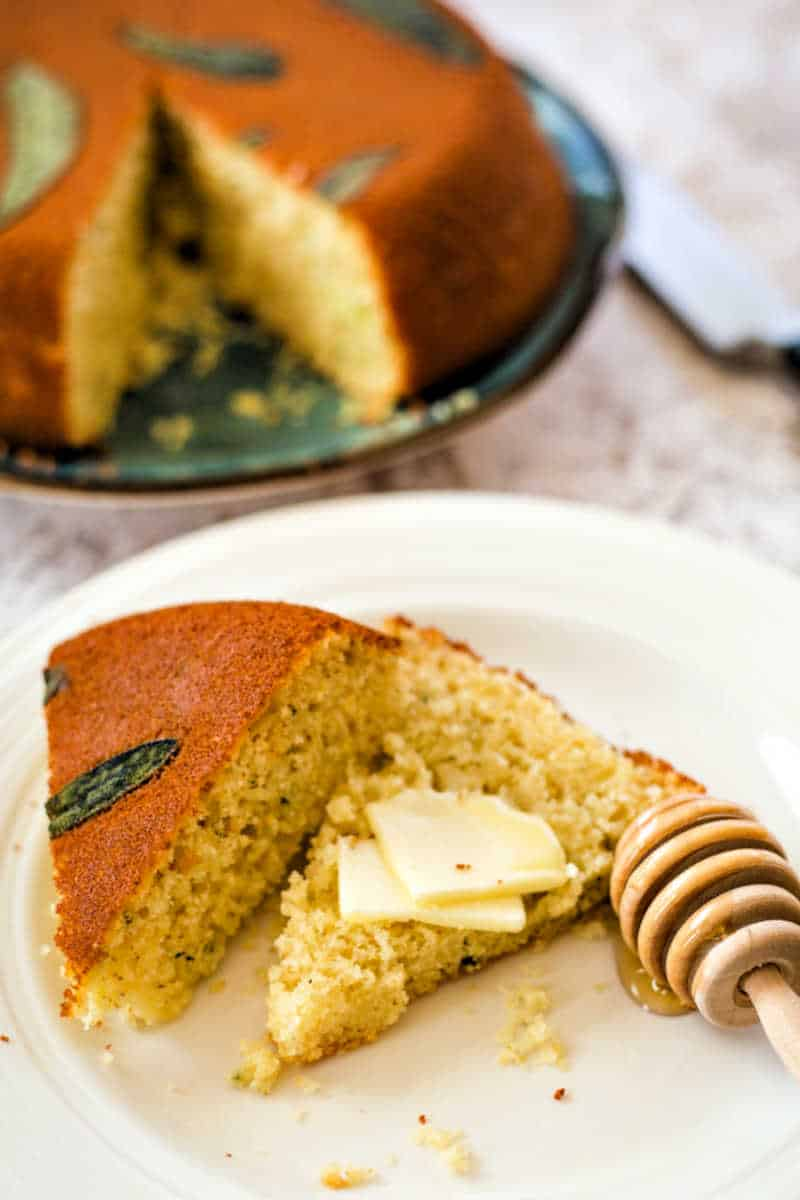 Honey Cornbread with Sage sliced open on a white plate with a honey spoon