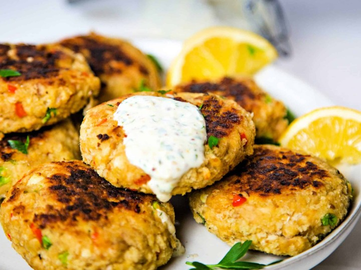 A plate of salmon patties with lemon slices