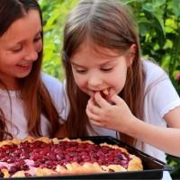 two little girls eating cherry pie in a garden