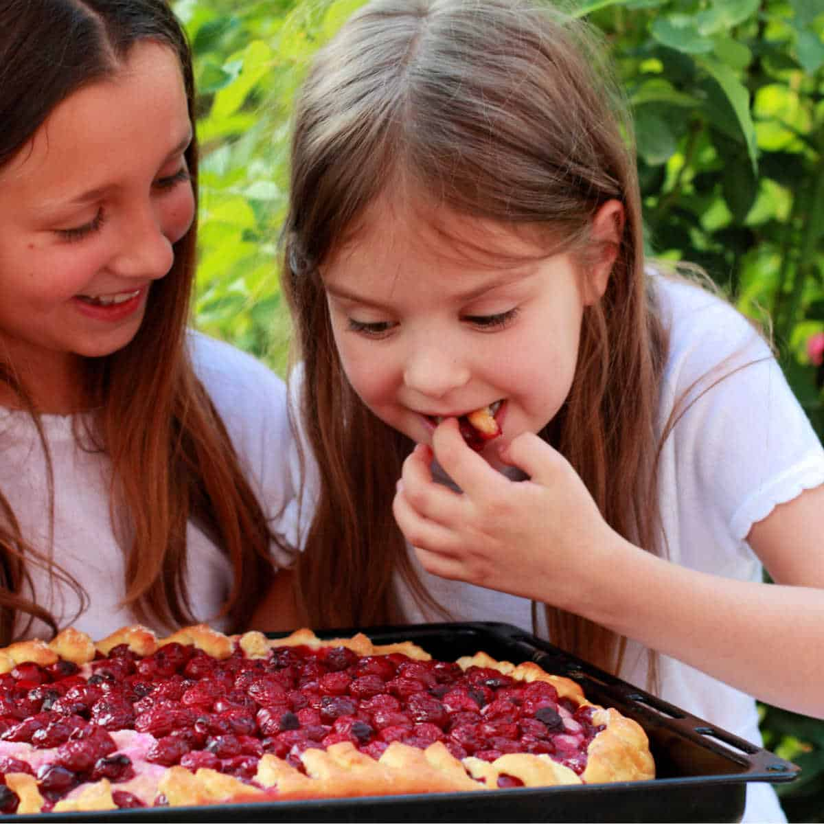 two little girls eating cherry pie in a garden