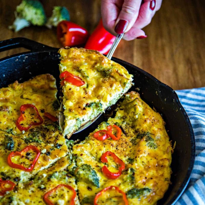 lifting a slice of broccoli frittata out of a cast iron sillet