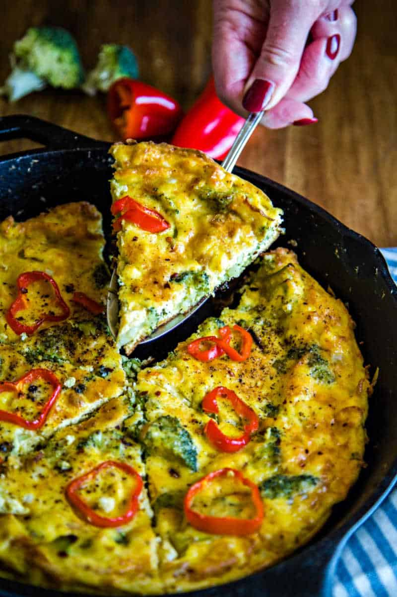 lifting a slice of broccoli frittata out of a cast iron skillet