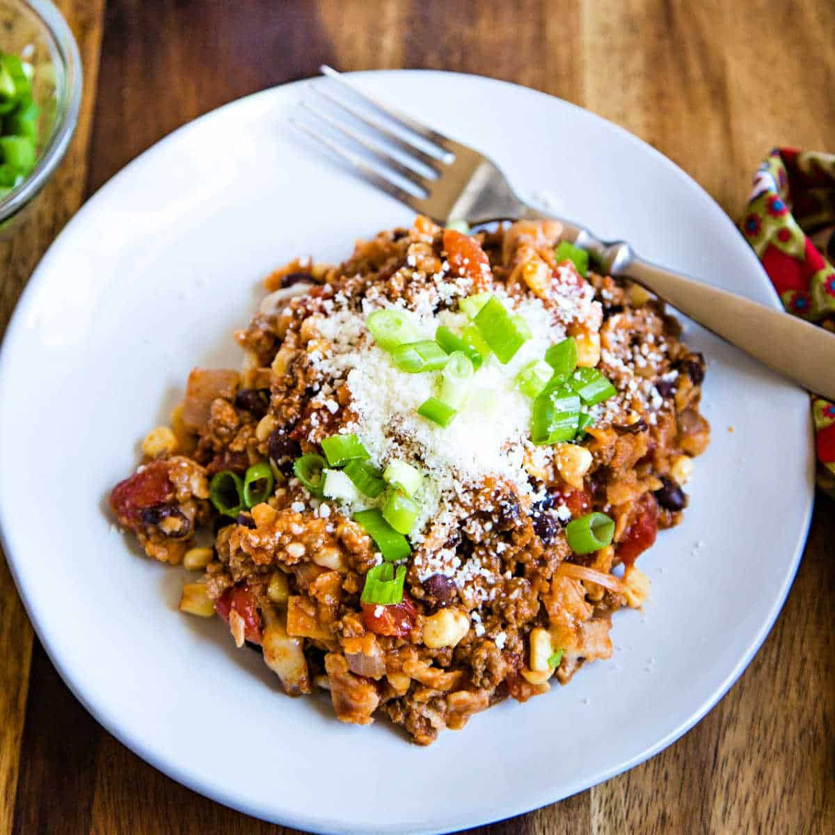 beef enchilada skillet topped with cojita cheese and green onions