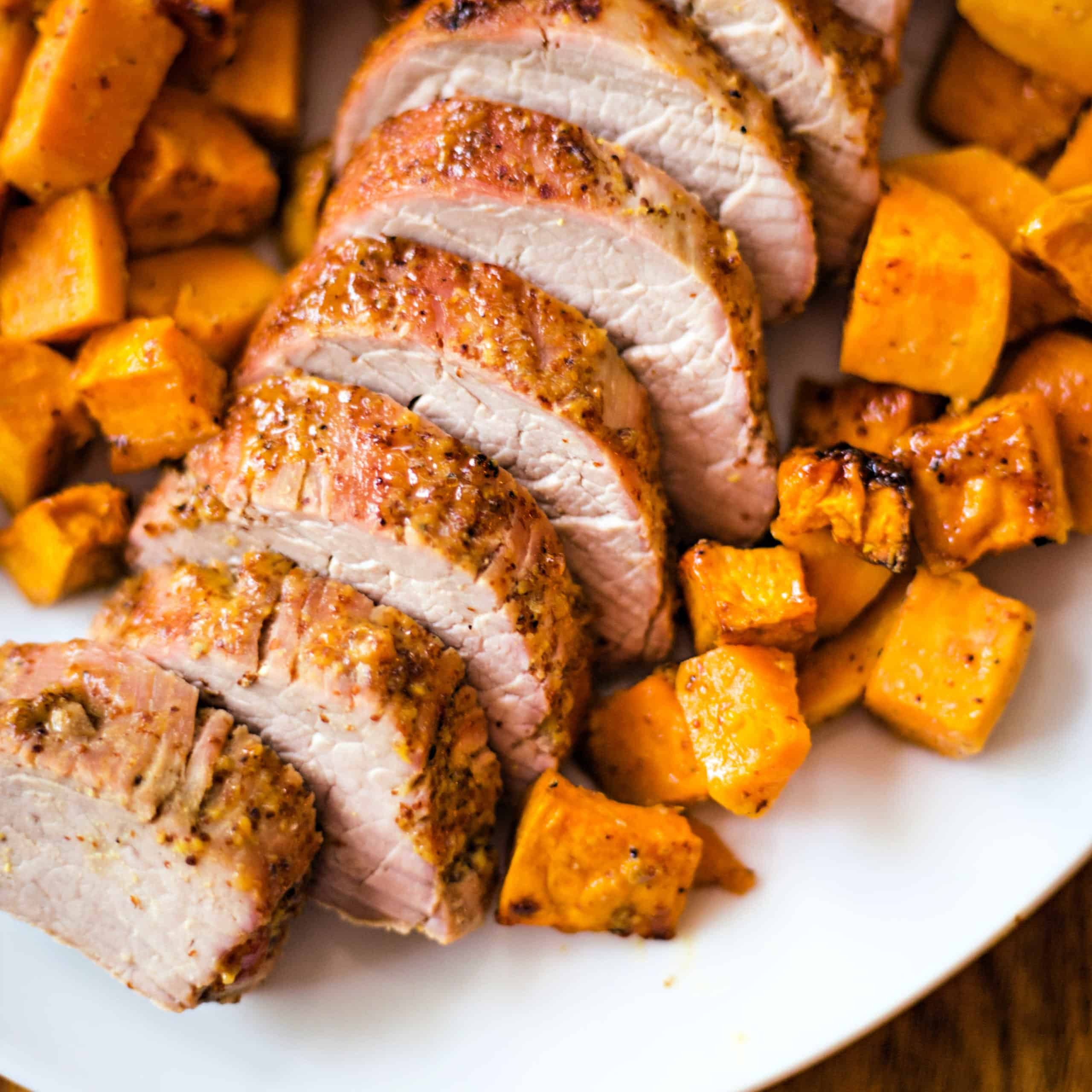 sliced Maple Dijon Oven-Roasted Pork Tenderloin with sweet potatoes on a white platter