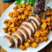 Maple Dijon Oven-Roasted Pork Tenderloin with sweet potatoes on a white platter