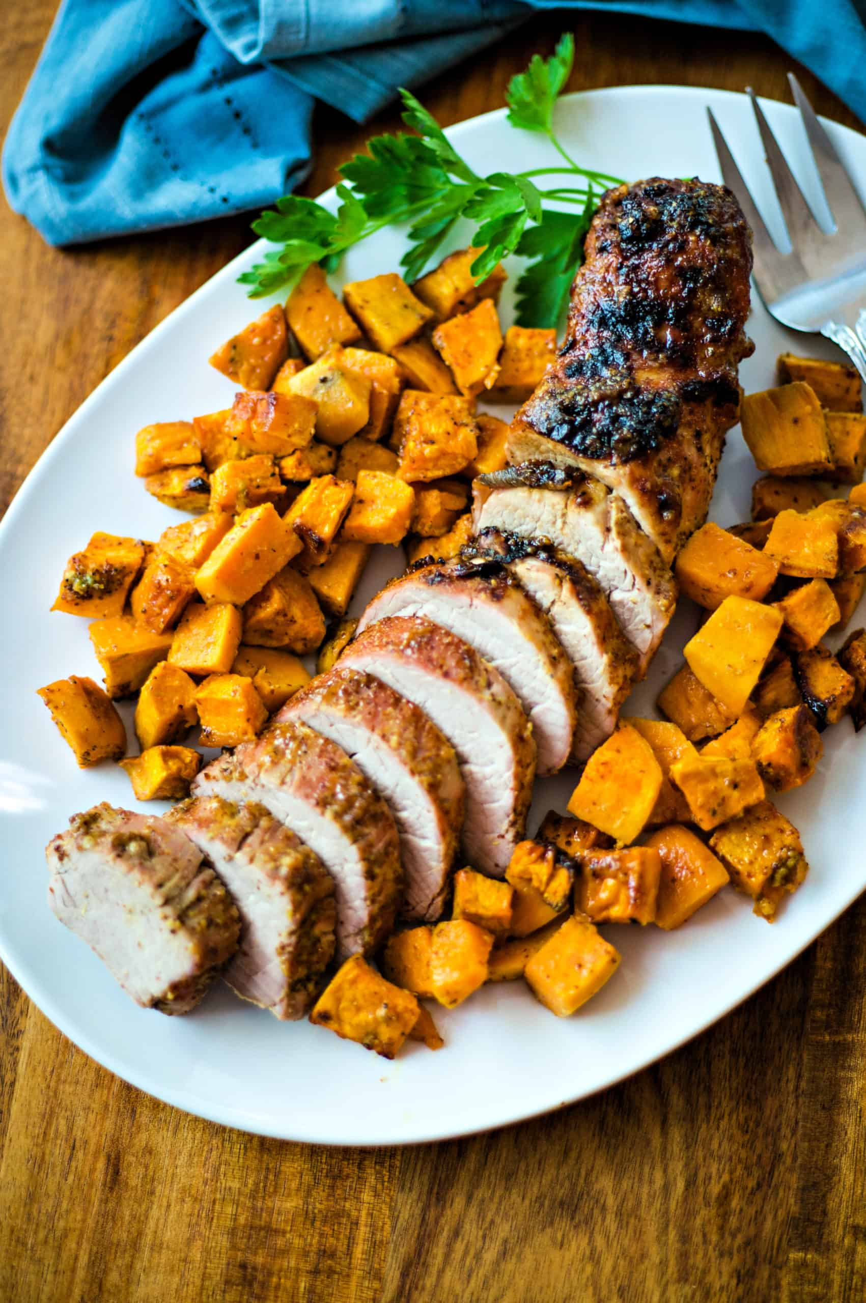 Maple Dijon Oven-Roasted Pork Tenderloin with sweet potatoes on a white platter