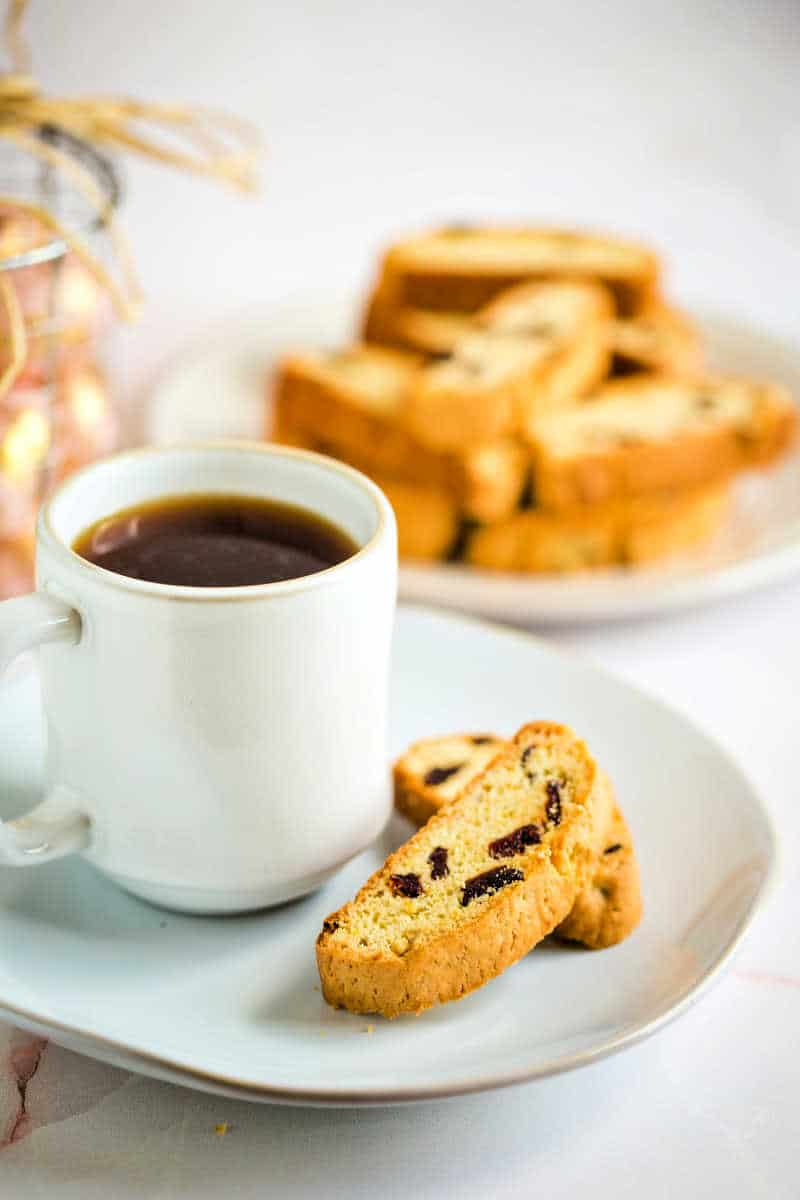 cherry biscotti on a plate with a cup of coffee