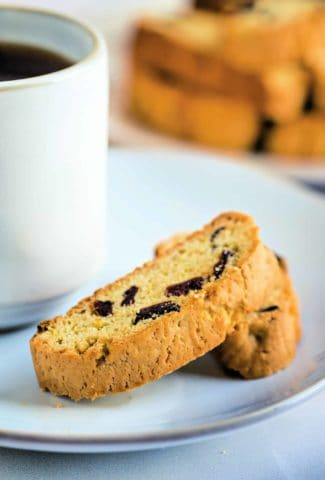 two pieces of cherry biscotti on a white plate with a cup of coffee