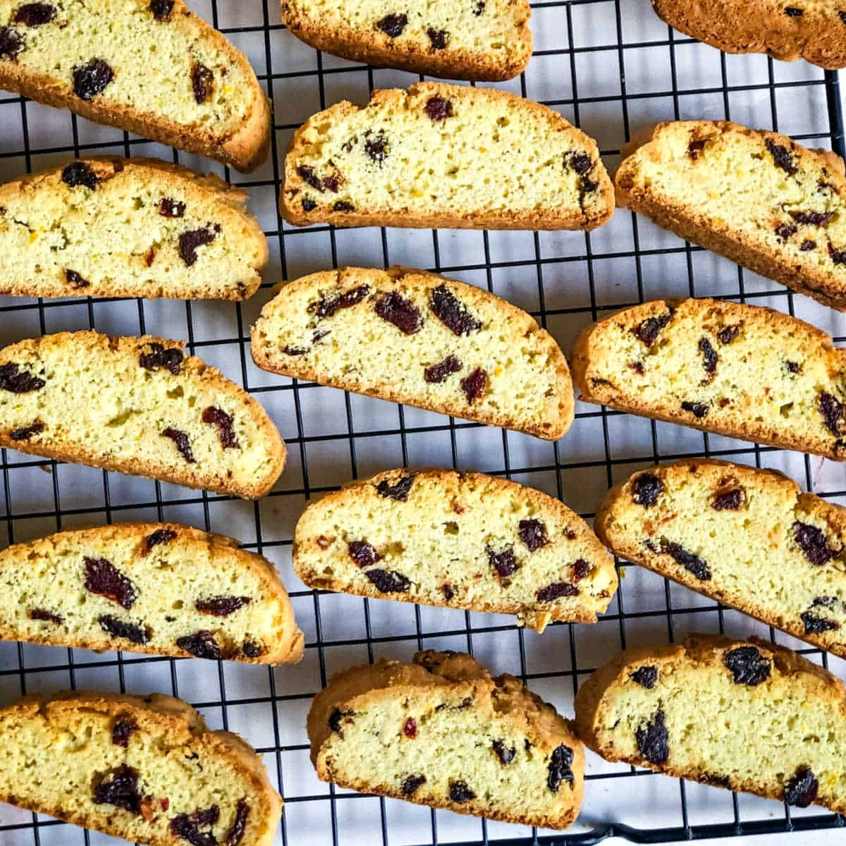 sliced cherry biscotti cooling on a wire rack