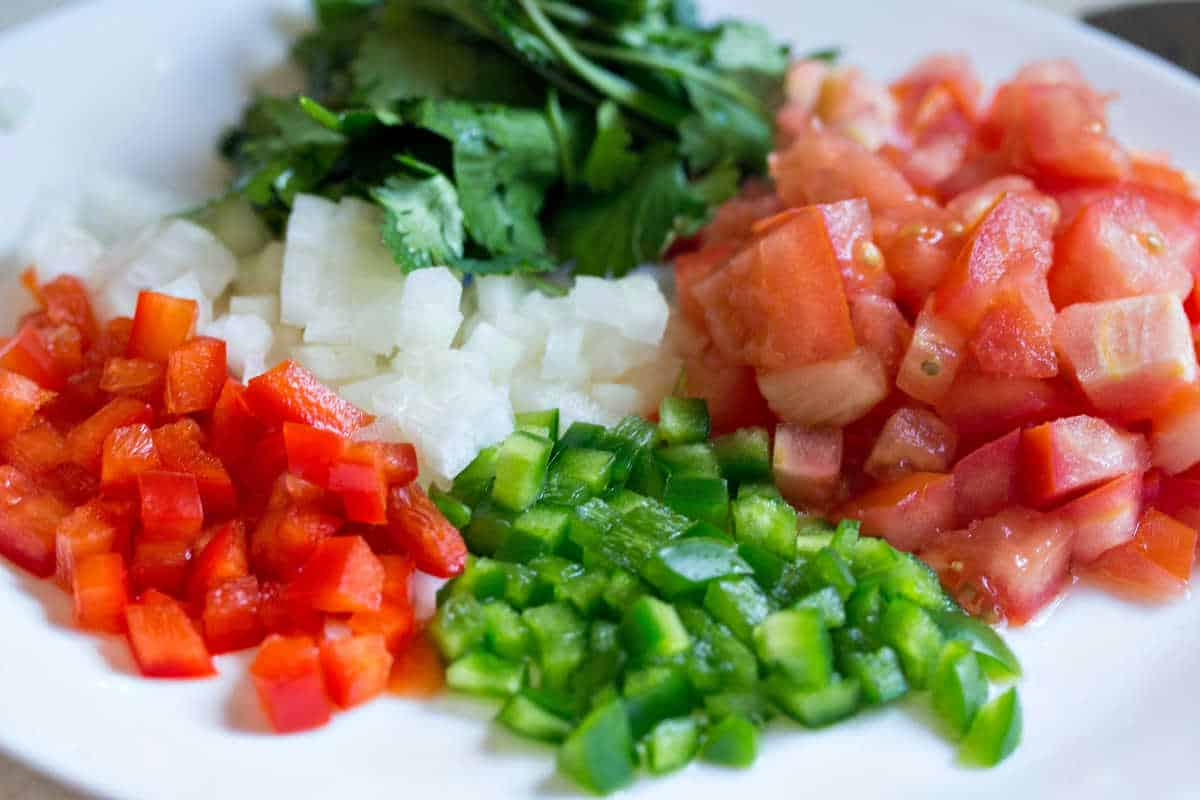 a plate of diced peppers, onions, tomatoes, and cilantro
