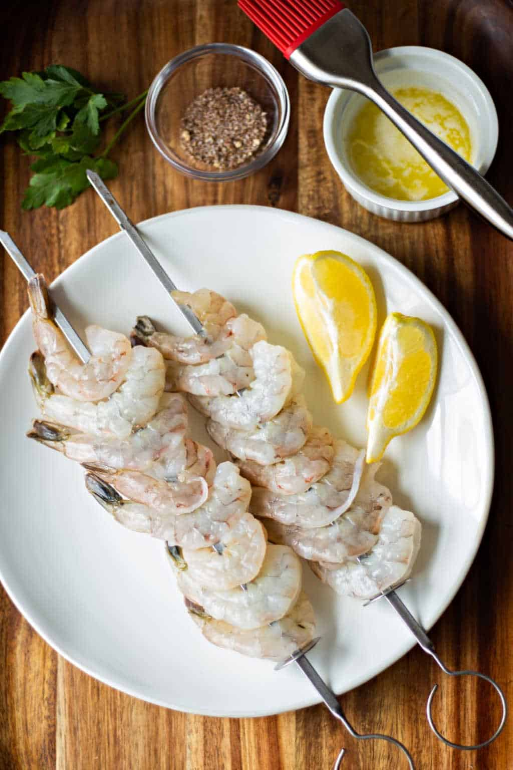 raw shrimp on skewers on a white plate with lemon slces