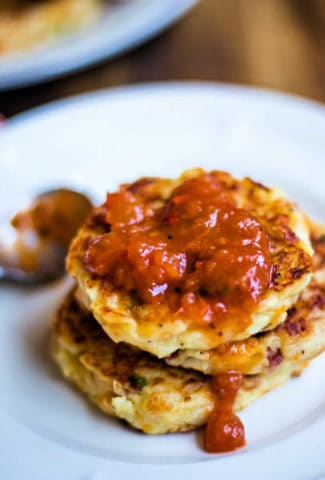 A plate of food on a table, with Tex-Mex mashed potato cakes