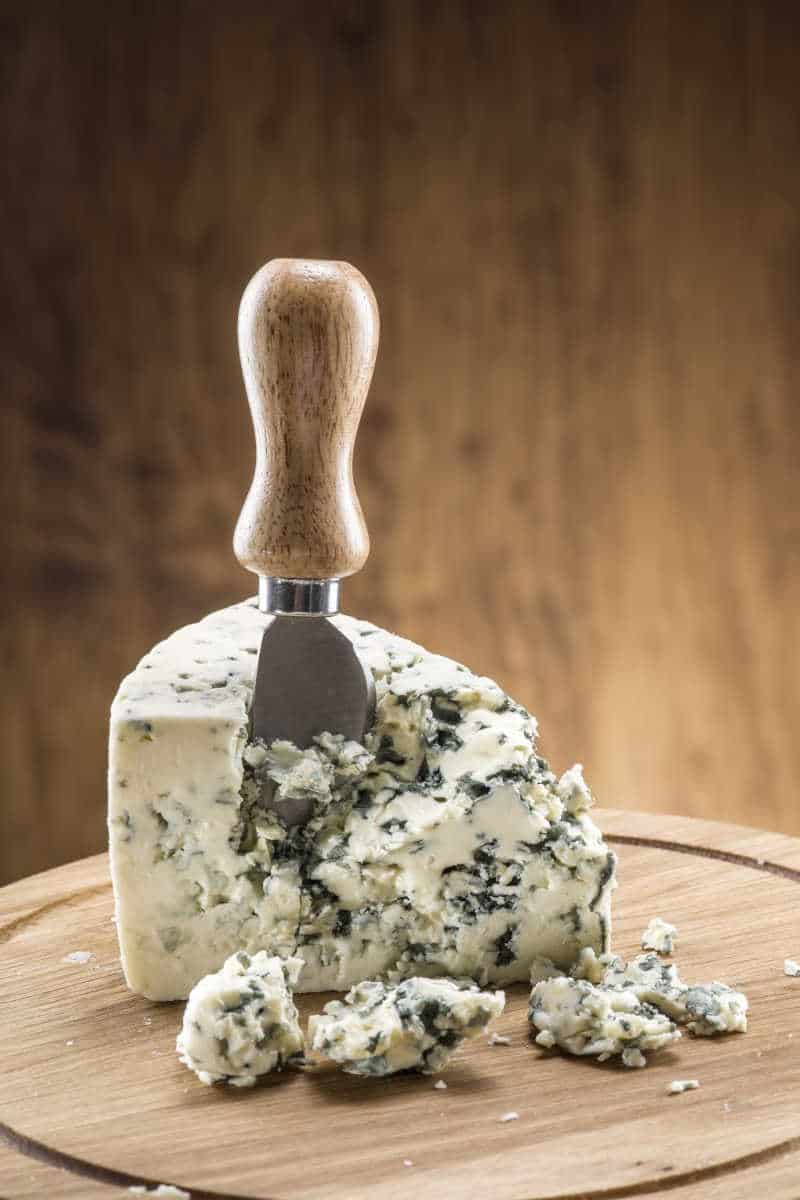 a wedge of blue cheese on a cheese board