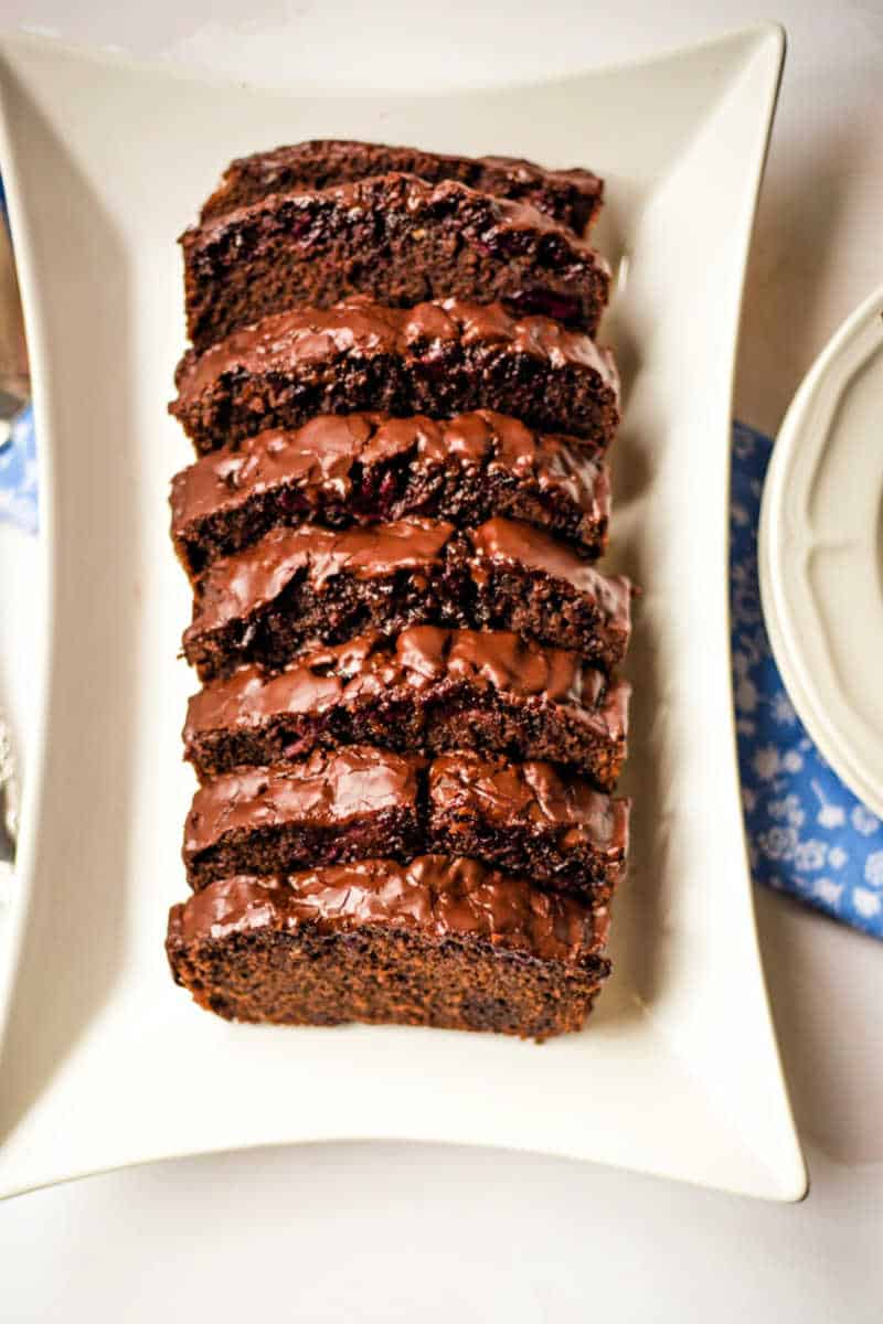 chocolate cherry loaf cake sliced and on a platter