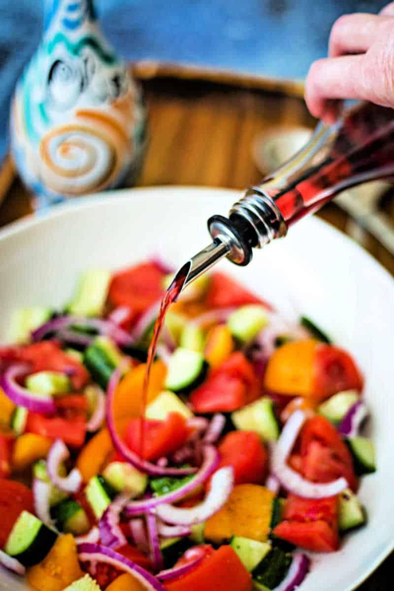 adding red wine vinegar to cucumber tomato feta salad
