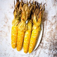 grilled corn in husk on a white platter