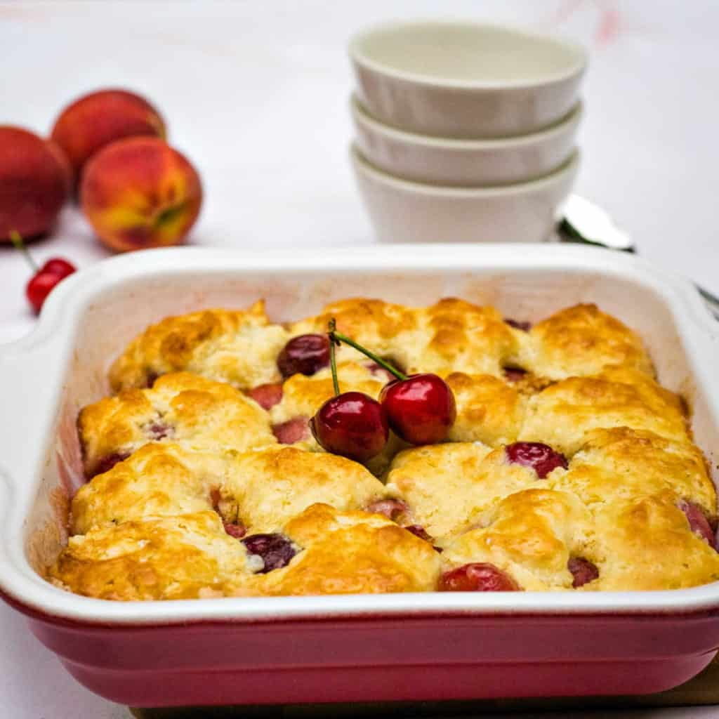 peach cherry cobbler in a baking dish with serving bowls