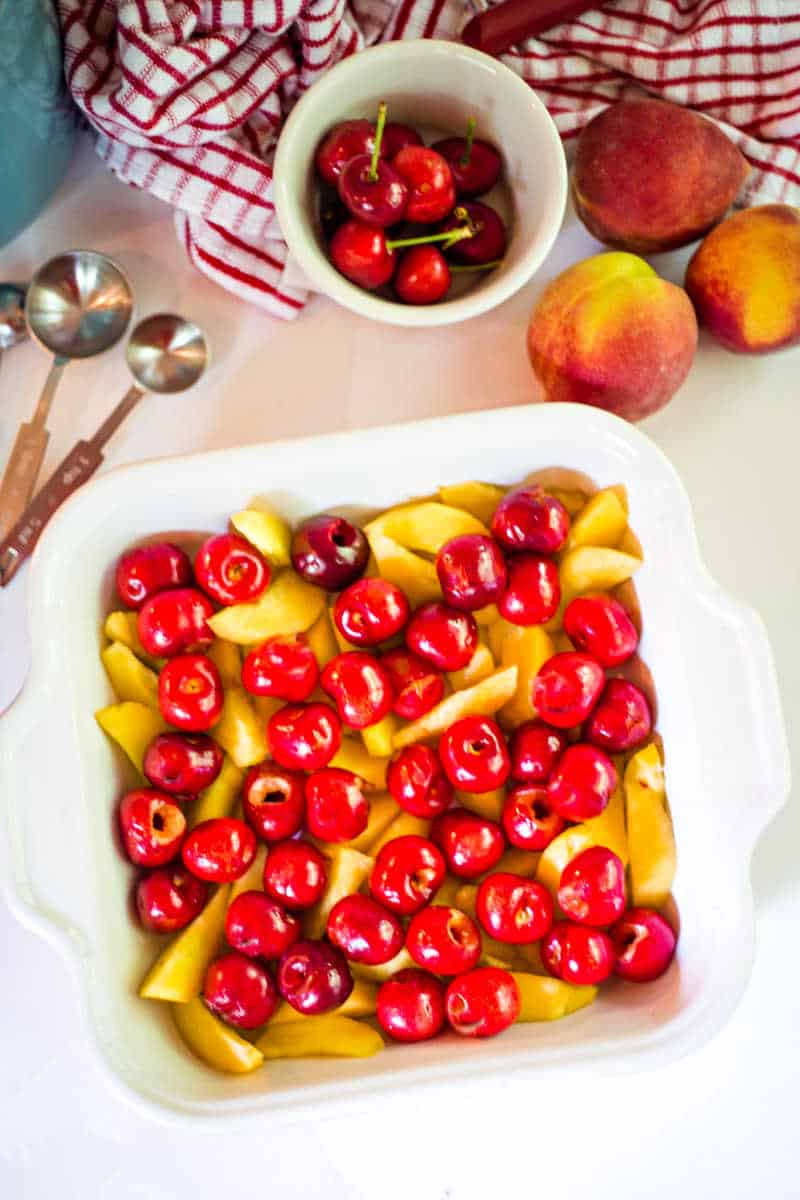 preparing cherry peach cobbler with fresh fruit in baking dish