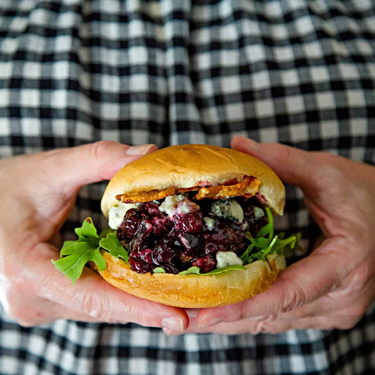 two hands holding a Blueberry Blue Cheese Bacon Burger on a white plate