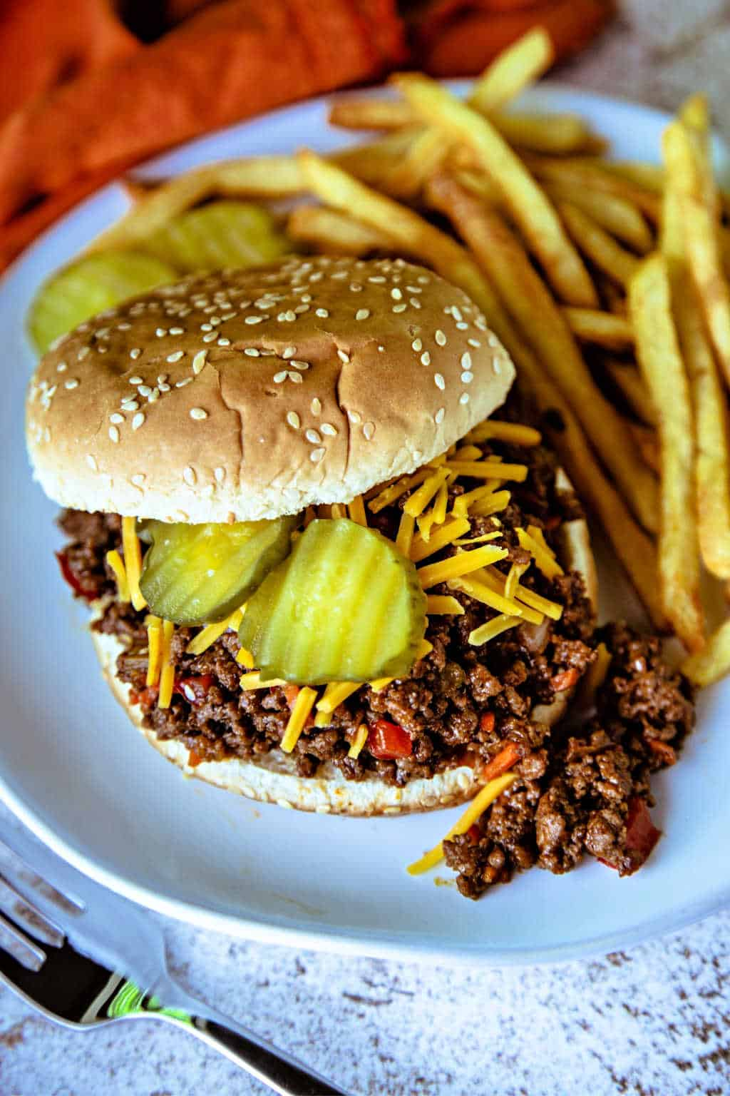 Sloppy Joe Sandwich on a white plate with french fries and topped with cheddar cheese and dill pickles