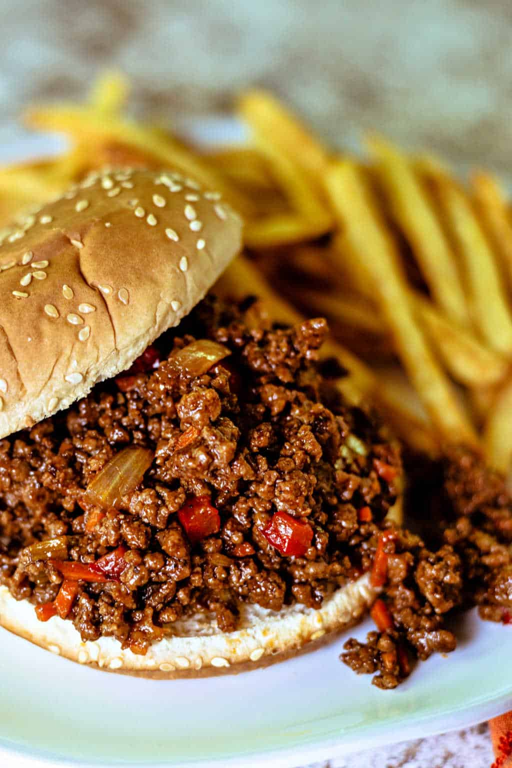 Sloppy Joe Sandwich on a white plate with french fries