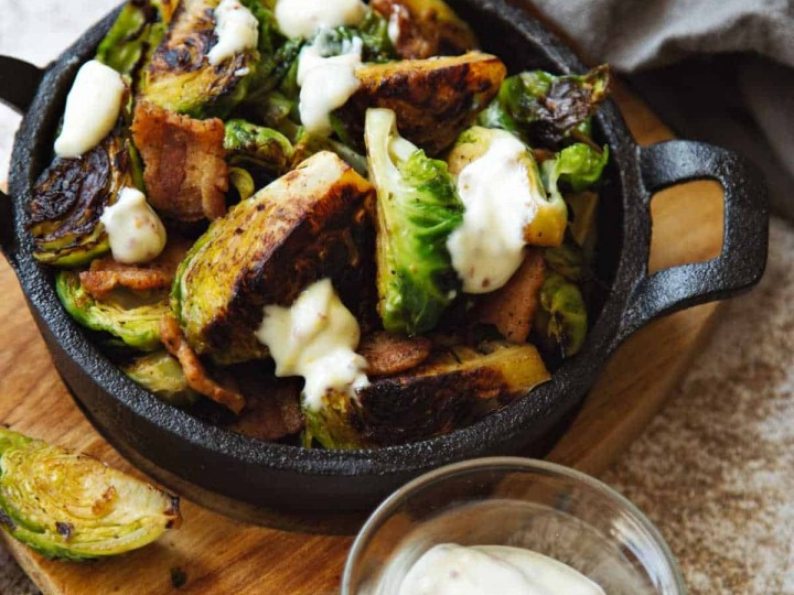 a cast iron skillet with charred brussel sprouts drizzled with garlic aioli