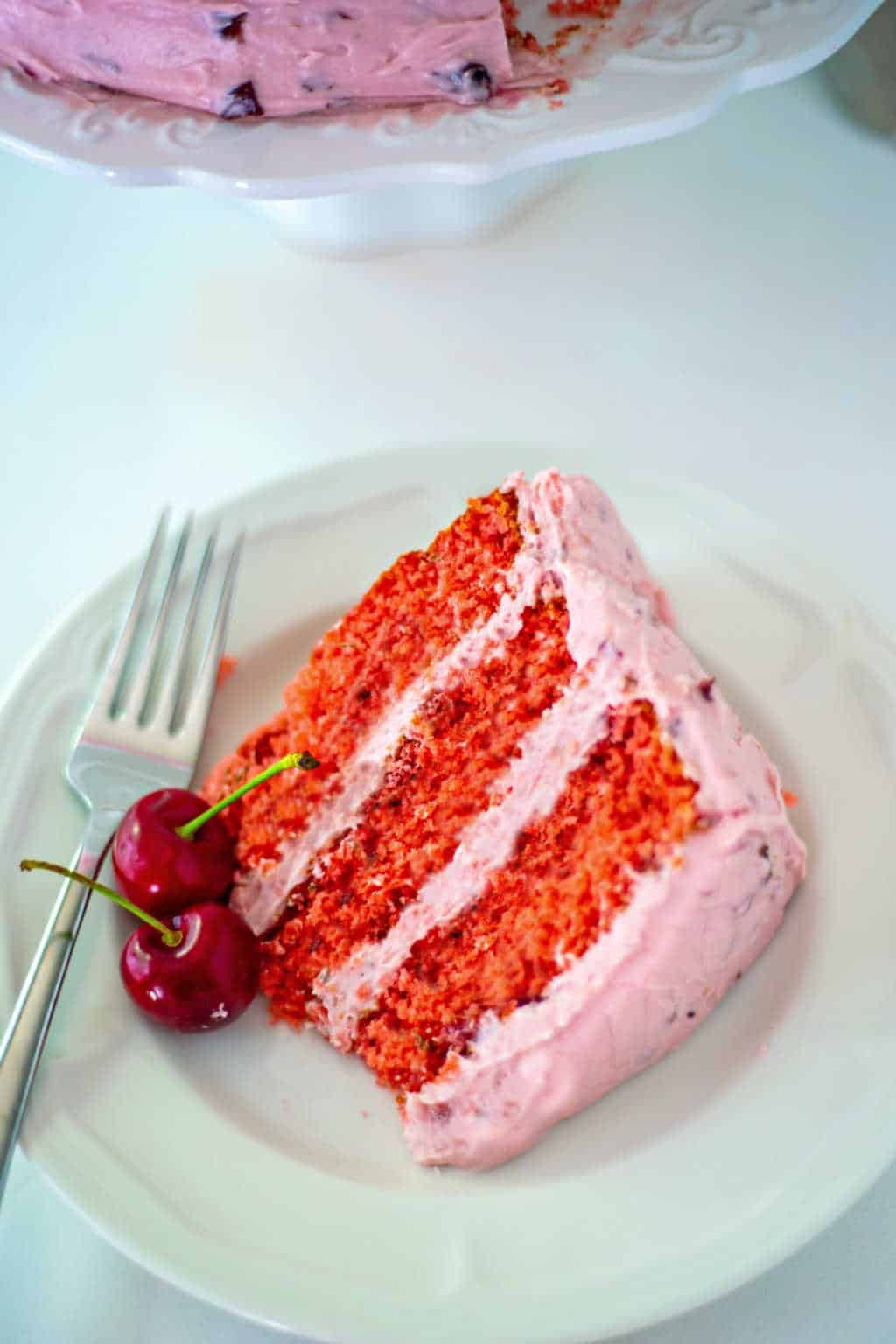 a slice of fresh cherry cake with fresh mint and buttercream frosting on a white plate with a fork and fresh cherry garnish