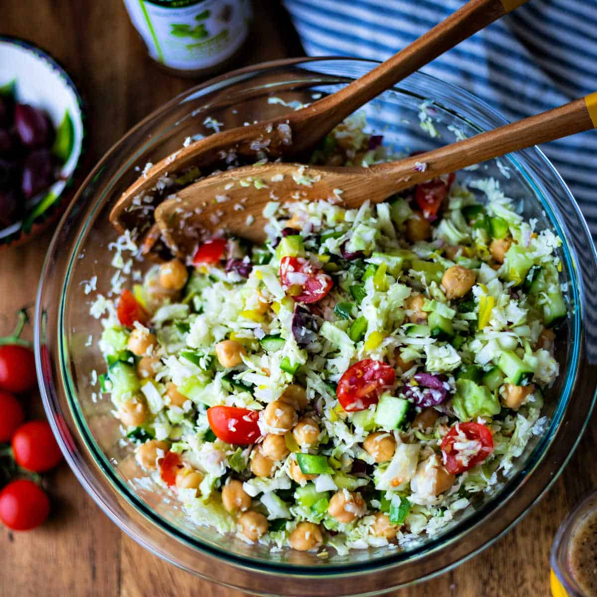 tossing healthy greek coleslaw with salad spoons