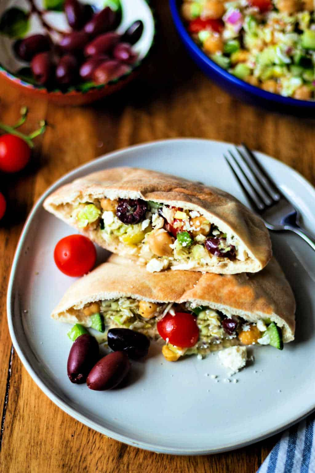 healthy greek coleslaw in pita pockets on a white plate with kalamata olives