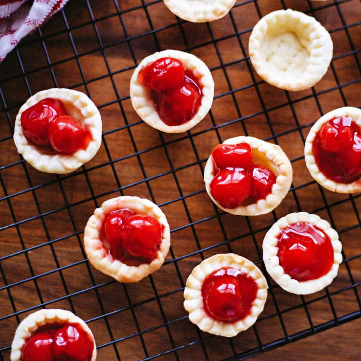 bite size cherry tarts on a cooling rack