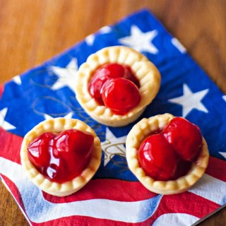 3 bite size cherry tarts on a patriotic napkin