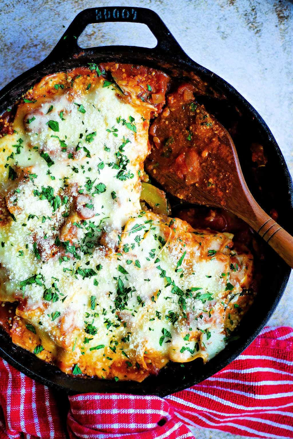 Skillet Lasagna with Squash and Mushrooms in a cast iron skillet with a wooden spoon