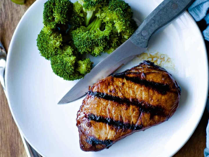 grilled pork chop on white plate with steak knife and broccoli