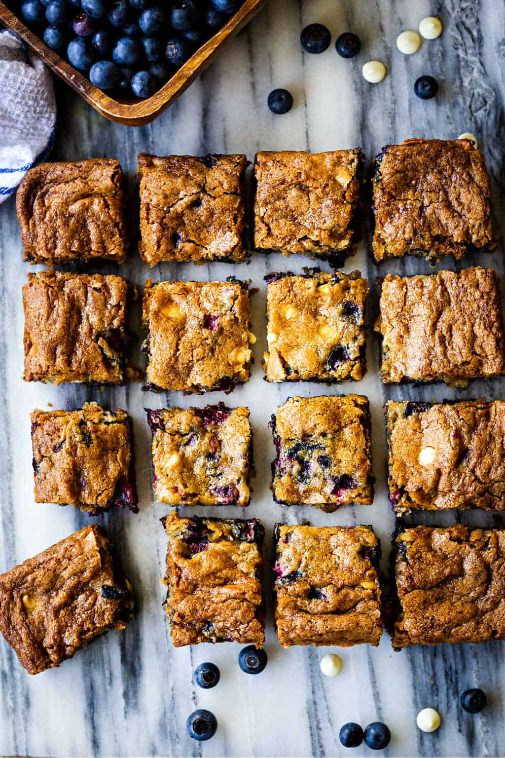 blueberry white chocolate chip cookie bars cut and separated into squares on a marble pastry board