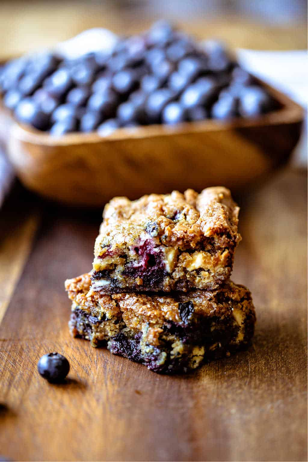 blueberry white chocolate chip cookie bars with a bowl of blueberries in the background
