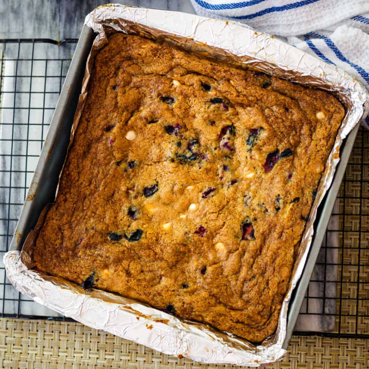 blueberry white chocolate chip cookie bars in an aluminum foil lined pan on a cooking rack