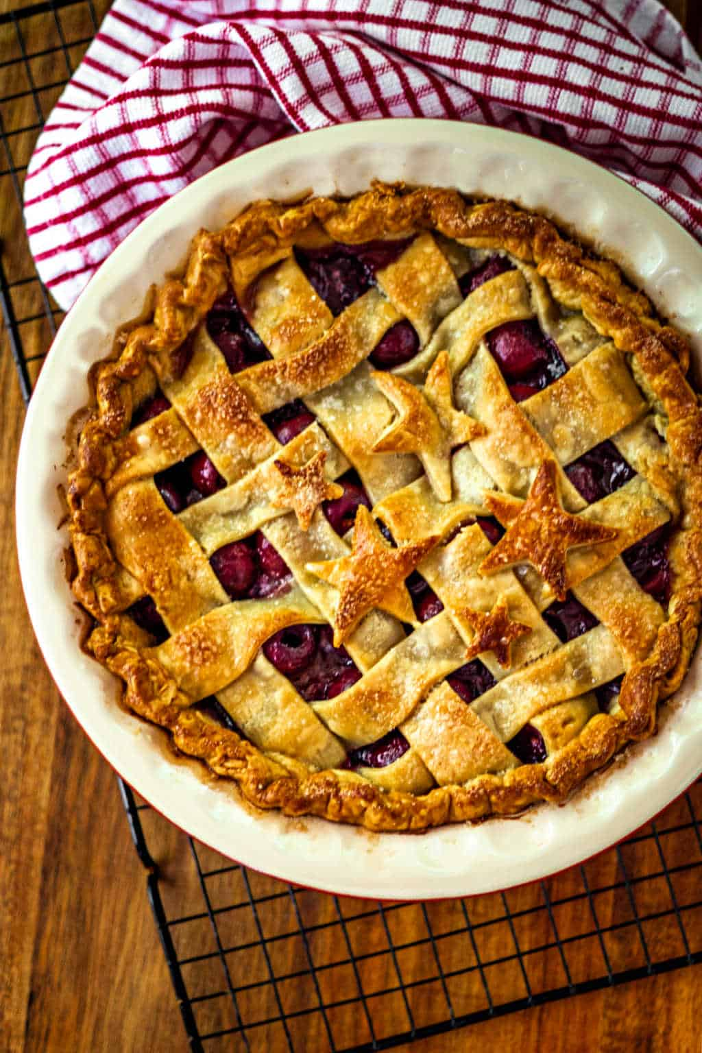 5-Star Cherry Pie with a lattice crust on a wire rack with a red and white kitchen towel