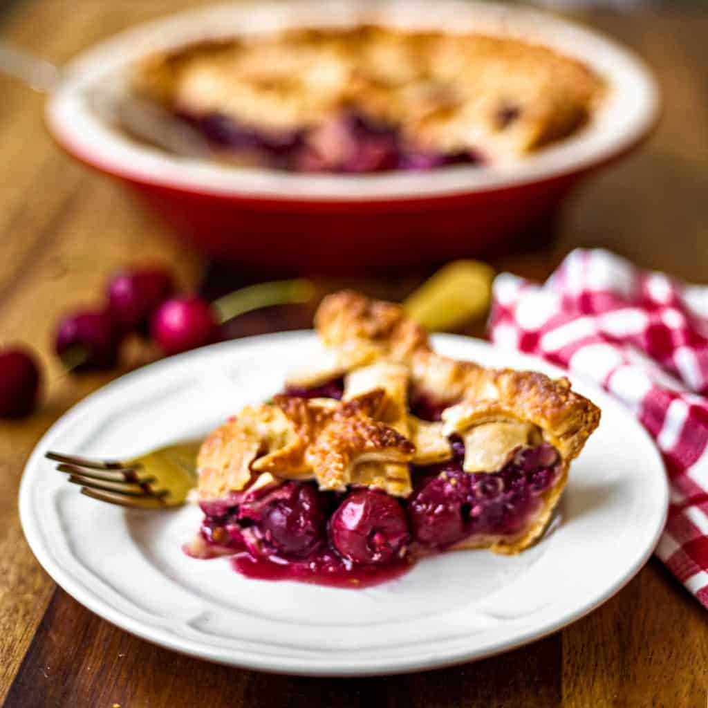 a slice of 5-star cherry pie on a white plate with a gold fork